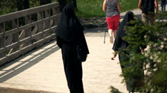 Nuns hiking, passing bridge, super slow motion 240fps Stock Footage