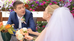 Handsome groom telling something to his beautiful bride sitting at a table in Stock Footage