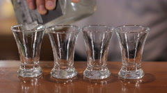 Bartender pours four shots of alcohol. Close up - stock footage