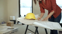 Woman worker making notes on blueprints at her new home Stock Footage