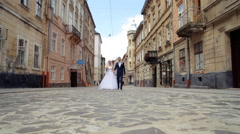 Smiling bride in white dress and veil and groom wearing blue suit walking down Stock Footage