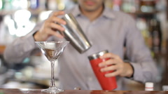 Bartender pours coctail from shaker into a glass. Medium shot Stock Footage
