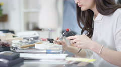 4K Jewelry designer working in studio with tools, materials & jewelry items Stock Footage