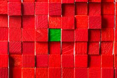 Wall of red toy blocks, green block in the middle Stock Photos