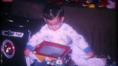 Young boy gets an Etch A Sketch on Christmas - 3339 vintage film home movie Stock Footage