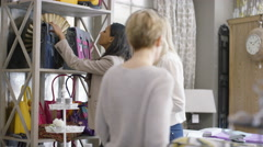 4K Female friends shopping together, looking at handbags in boutique store - stock footage