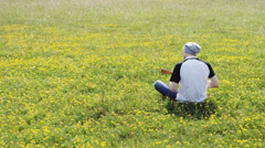 4K Back of a young man playing a guitar sat in a field of yellow flowers Stock Footage