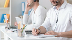 Positive handsome man working in the call center Stock Footage