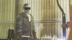 Worker protective clothing and glasses standing next to a running plasma machine Stock Footage