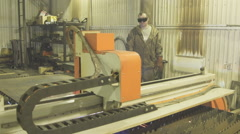 Worker in protective suit and glasses oversees work of plasma machine Stock Footage