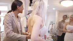 4K Beautiful bride to be trying on wedding gown in store with sales assistant - stock footage