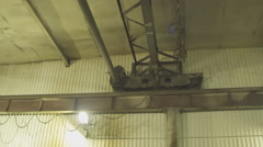 Electric hoist moves slowly under roof of plant Stock Footage