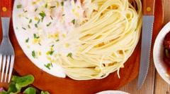 Wild salmon baked in cream cheese sauce with italian pasta on wo Stock Footage