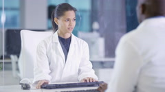 4K Portrait female scientist working on computer in front of glass screen Stock Footage