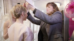 4K Bride to be & her mother trying on gowns in bridal store with sales assistant Stock Footage