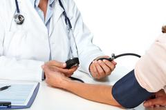 Doctor woman measuring patient blood pressure. - stock photo