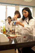 Scientist heating liquid in beaker Stock Photos