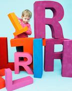 Toddler playing with oversize letters - stock photo