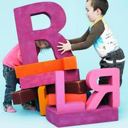 Toddlers playing with oversize letters - stock photo