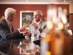 Business men drinking whisky at bar in lounge Stock Photos