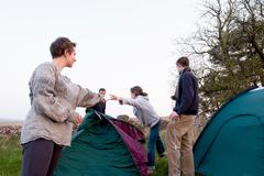 People pitching tents at campsite Stock Photos