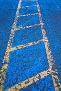 Yellow road marking on blue asphalt - stock photo