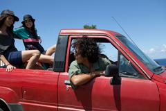 Three young friends driving off road vehicle on vacation - stock photo
