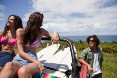 Three young friends in off road vehicle with surfboards - stock photo
