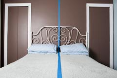 Double bed separated by blue line Stock Photos