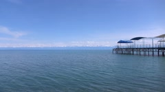Empty pier, lake and distant snow peaks on the horizon. 4K sunny day pan shot Stock Footage