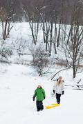 Mother and daughter sledging in snow Stock Photos