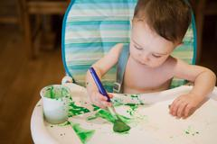 Baby boy sitting in high chair painting picture - stock photo