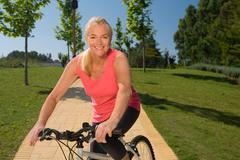 Mature woman cyclist with bicycle - stock photo