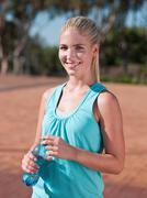 Young woman holding bottle of mineral water - stock photo