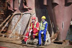 Workers sitting on rope on oil rig - stock photo