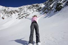 Woman skiing backwards down slope Stock Photos