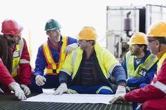 Workers examining blueprints on oil rig - stock photo