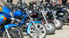 Motorcycles aligned in a row at motorcycle rally Stock Footage
