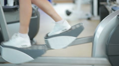 Girl in gym on simulator. The woman with athletic legs walking on the steppers Stock Footage