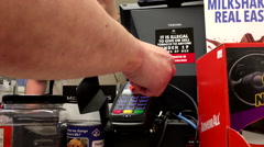 Man tapping Tangerine credit card to buy lottery ticket inside husky gas station - stock footage