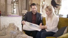 4K Couple with sales assistant, looking at fabrics in home furnishings store Stock Footage