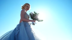Happy bride on a background of blue sky in the light of the sun with flowers. - stock footage