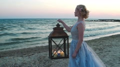 Lonely girl waiting for a loved one on the beach with a lantern in her hand. Stock Footage