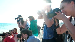 Group of photographers with SLR cameras take pictures of the sea on the coast. Stock Footage