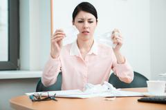 Woman in office with crumpled paper - stock photo