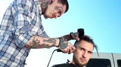 Tattooed racy hairdresser doing haircut guy on the street clipper. Stock Footage