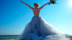 The girl in a wedding dress raises her hands with flowers up against the sea. Stock Footage