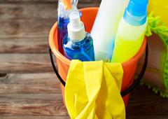 Plastic bucket with cleaning supplies on wood background Stock Photos
