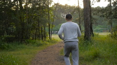 Young sports man in the baseball cap runs through the woods - stock footage