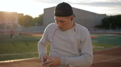 Slowmotion of young man wears headphones on field at sunset on stadium track - stock footage
